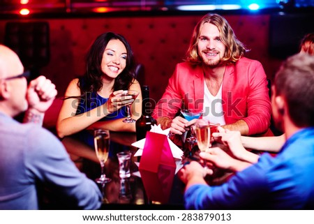 Group of happy friends sitting by table at restaurant