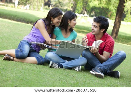 Group of happy friends sitting in lawn - stock photo