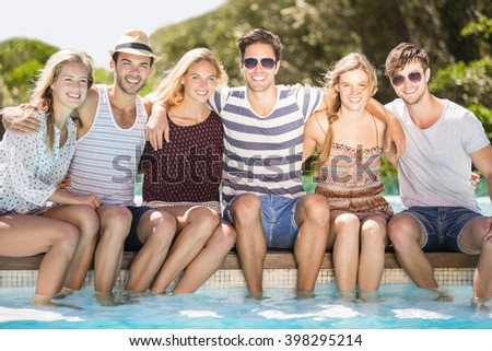 Group of happy friends smiling and sitting side by side at poolside