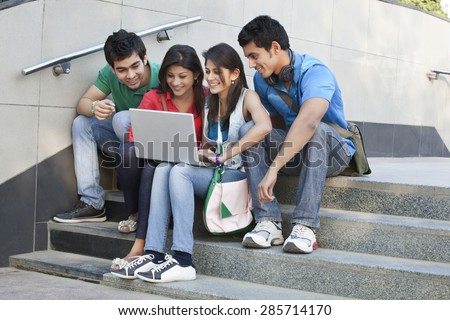Group of happy friends surfing net while sitting on steps - stock photo