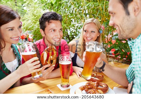 Group of happy friends talking in beer garden in summer in Bavaria - stock photo