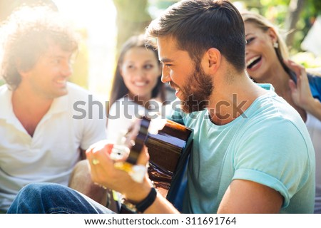Group of happy friends with guitar having fun outdoor - stock photo