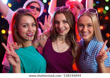 Group of happy girls posing in the night club