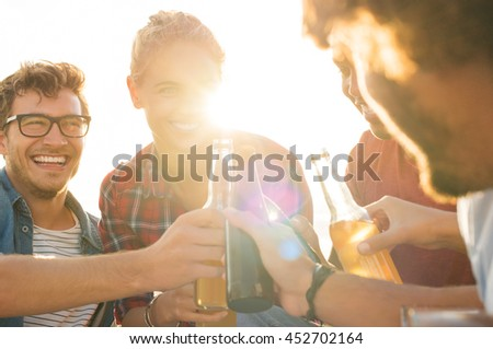 Group of happy guys and girls enjoying a drink during sunset at beach. Smiling friends raising a toast while drinking beer from bottle, summer vacation. Multi ethnic group of people drinking beers.