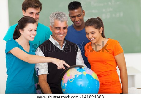 group of happy high school students and teacher looking at globe - stock photo