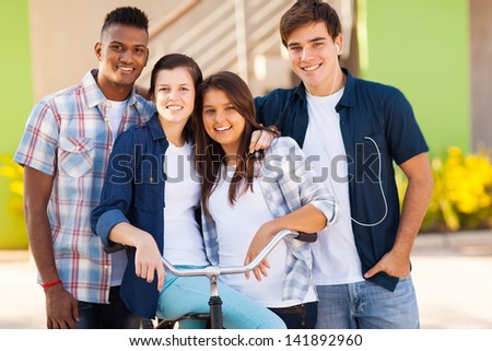 group of happy high school students with a bicycle outdoors - stock photo