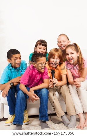 Group of happy kids, boys and girls, singing on karaoke together sitting on the coach in living room - stock photo