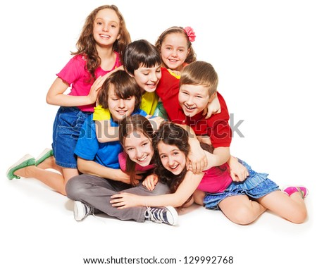 Group of happy kids - boys and girls sitting together, hugging, laughing