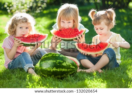 Group of happy kids eating watermelon on green grass in summer park