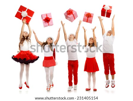 Group of happy kids in Christmas hat catching gift boxes. Isolated on white background. Holidays, christmas, new year, x-mas concept. - stock photo