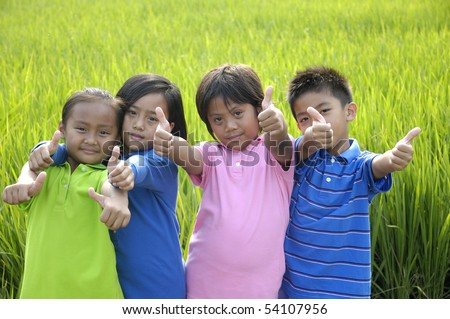 group of happy kids in the green rice fields - stock photo