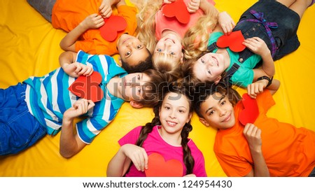 Group of happy kids laying in circle on the floor with hearts in their hands - stock photo