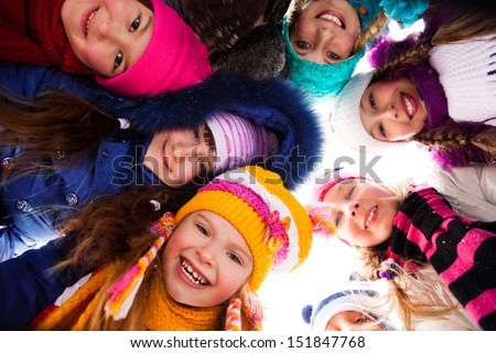 Group of happy kids look down wearing winter clothes - stock photo