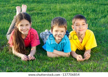 Group of happy kids lying on the green grass field - stock photo