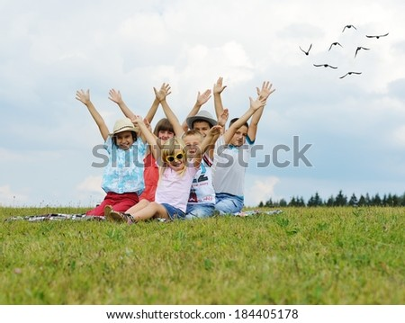 Group of happy kids on summer grass meadow in nature having fun - stock photo
