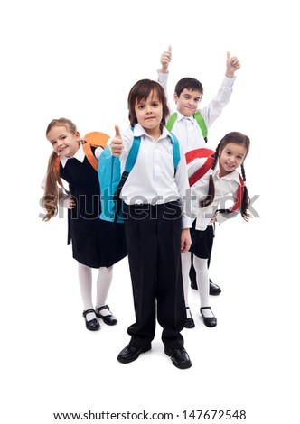 Group of happy kids with backpacks returning to school after summer vacation - stock photo