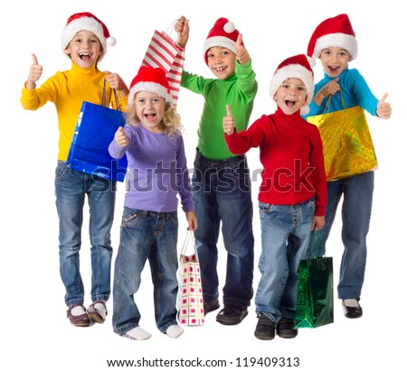 Group of happy kids with christmas gifts and thumbs up sign, isolated on white