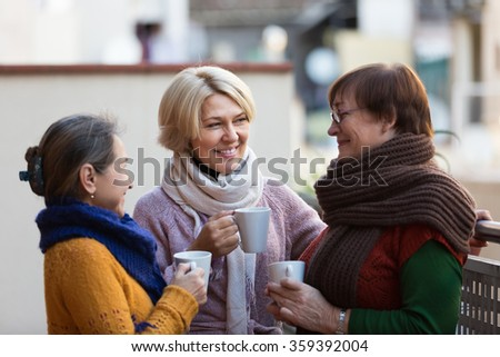 Group of happy mature women drinking tea at balcony