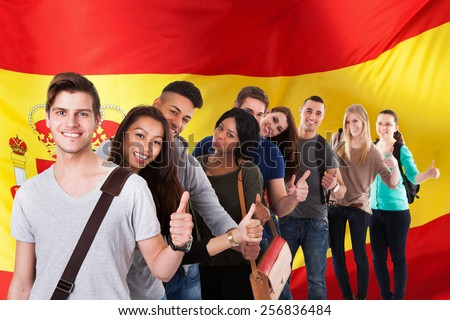 Group Of Happy Multi Ethnic Students Standing In Front Of Spain Flag Showing Thumb Up - stock photo