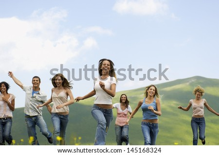 Group of happy multiethnic friends running against mountain - stock photo