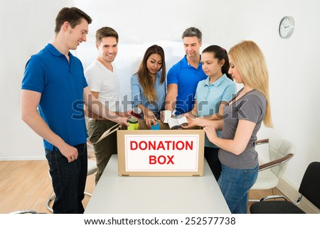 Group Of Happy Multiethnic People Putting Cans In Donation Box - stock photo