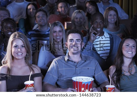 Group of happy multiethnic people with soda and popcorn watching movie in theatre