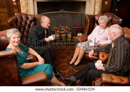 Group of happy older senior friends enjoying each others company in an expensive hotel