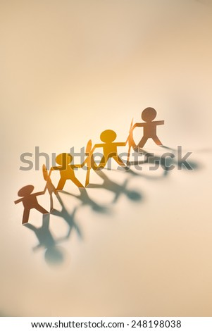 Group of happy people cut from paper holding hands in a warm tone.