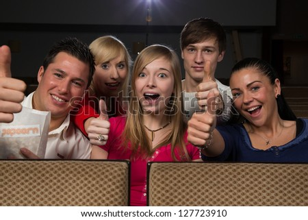 Group of happy people having fun in a cinema or movie theater