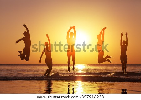 Group of happy people jumping in the sea at sunset, concept about having fun on the beach, silhouette - stock photo