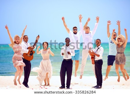 group of happy people on celebration the exotic wedding with musicians, on tropical beach - stock photo