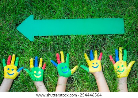 Group of happy people on green grass. Children having fun in spring. Smiley on hands. Teamwork concept. Top view portrait - stock photo