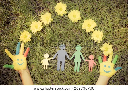 Group of happy people on green grass. Family having fun in spring. Smiley on hands. Ecology concept. Top view portrait. Retro toned image - stock photo