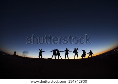 Group of happy people on top of a mountain in the Sahara desert, Morocco