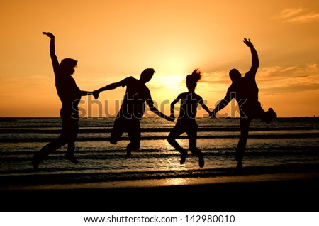 Group of happy people parting on the beach at sunrise, all holding hands and jumping of joy