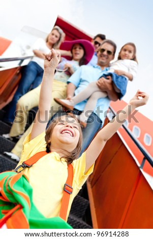 Group of happy people traveling by airplane going on holidays - stock photo