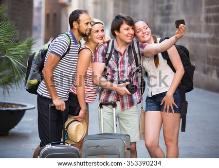 Group of happy russian tourists making selfie on the background of landmark - stock photo