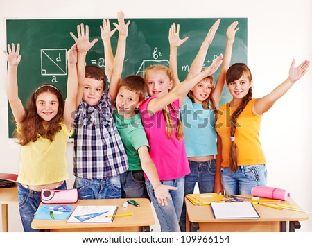 Group of happy school child  in classroom. - stock photo