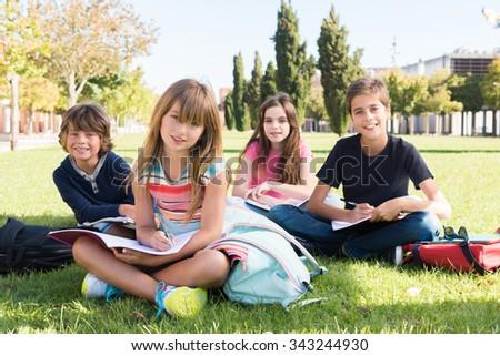 Group of happy school kids in school campus - stock photo