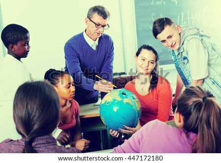 group of happy school pupils 16s taking a rest together indoors - stock photo