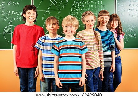 Group of happy schoolchildren at a classroom. Education. - stock photo