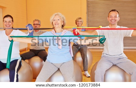 Group of happy senior people doing back training with exercise band in gym - stock photo
