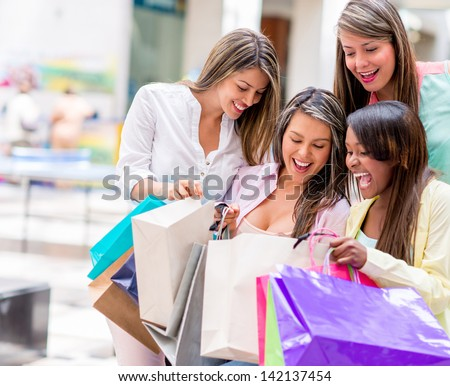 Group of happy shopping women looking in their bags - stock photo