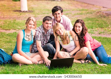 Group of happy smiling Teenage Students looking in laptop