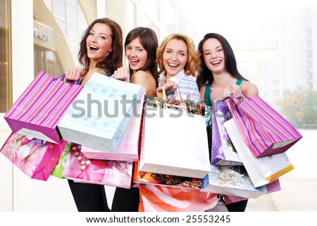 Group of happy smiling women shopping with colored bags