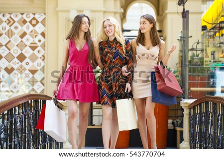 Group of happy smiling women shopping with colored bags walking in the mall