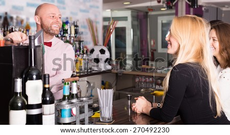 Group of happy smiling young adults hanging out in bar - stock photo