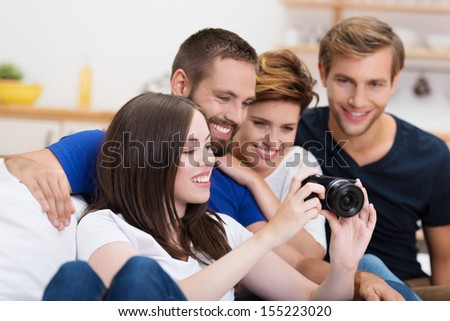 Group of happy smiling young friends checking out a photograph on the back of a camera as they sit together on a sofa