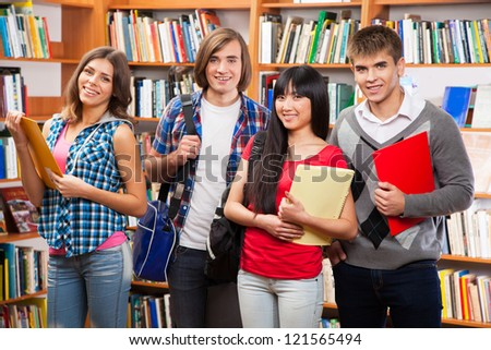 Group of happy students in a library - stock photo