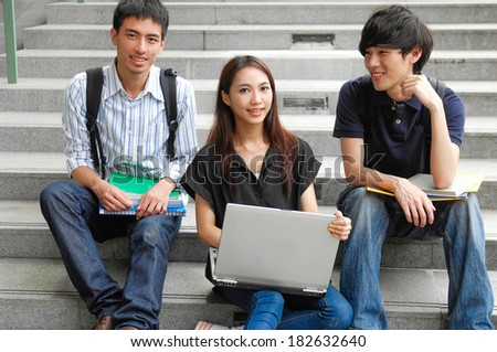 Group of happy students sitting on outdoor - stock photo